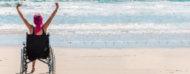 Mujer en silla de ruedas festejando frente a la playa