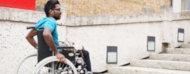 Hombre en silla de ruedas enfretado a una escalera.