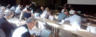 Personas trabajando con papeles en varias mesas